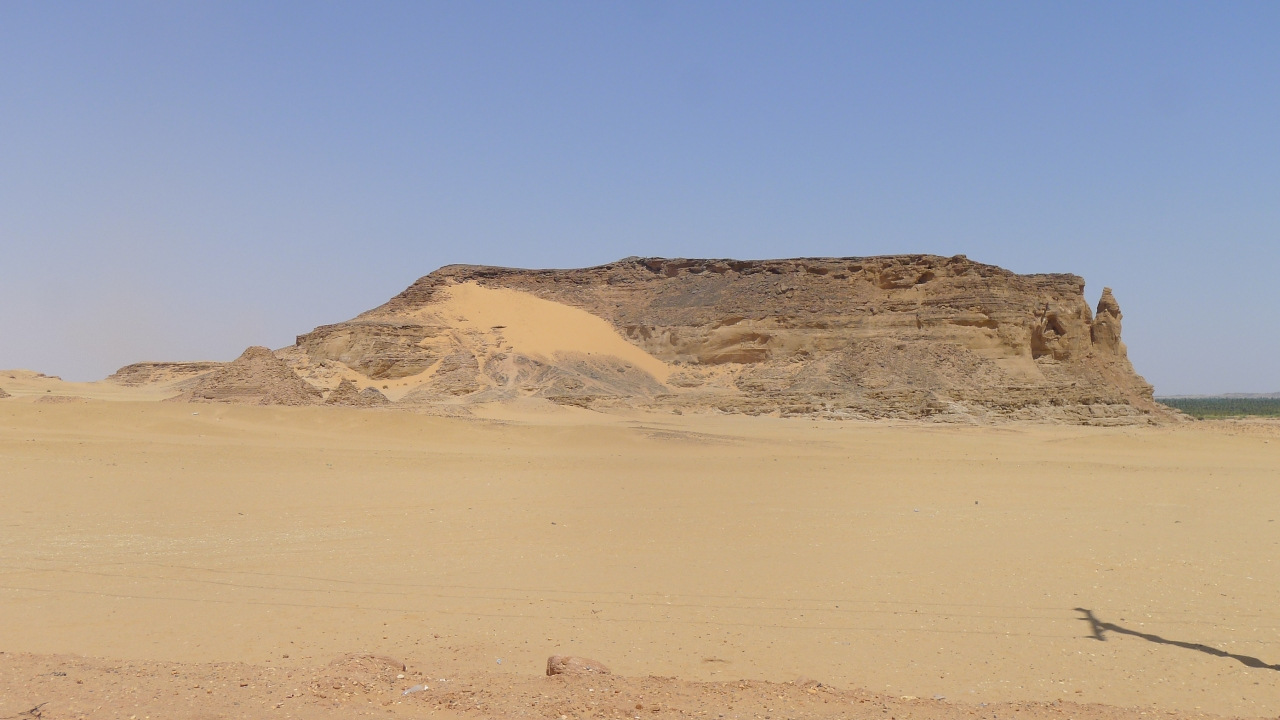 Riding past Jebel Barkal... extremely hot and Fanny's starter relay is having problems