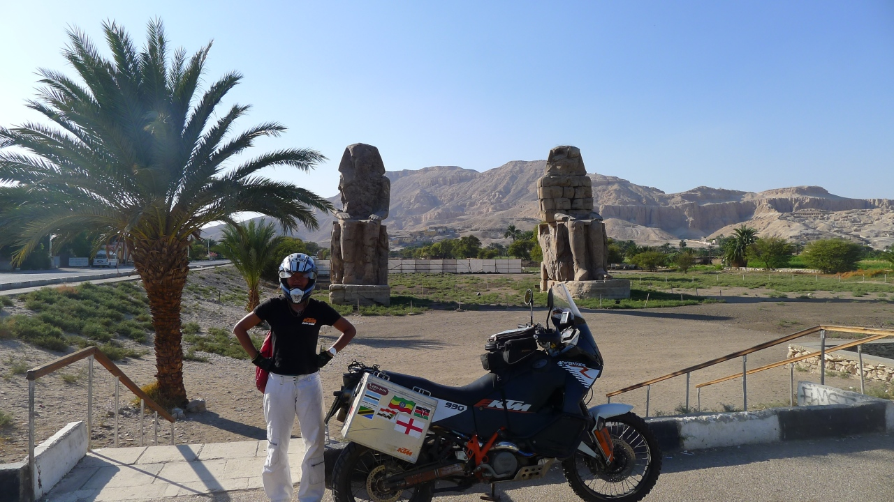 Posing against the ancient statues in Luxor near the valley of the Kings.