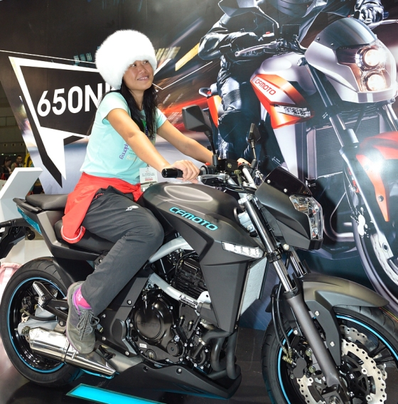 Fanny with her Tibetan white fox hat and the CF Moto 650 NK street bike that she will ride in Hong Kong.