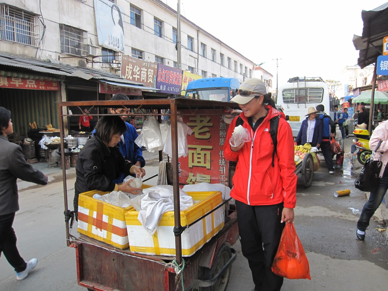 """Fanny eating """"mantou"""" (a kind a bread bun) from a hawker in the main town"""